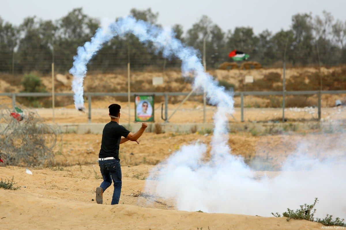 """Palestinians use slingshot to throw back tear gas canister towards Israeli security forces during a protest within the """"Great March of Return"""" near Israel-Gaza border, in eastern part of Rafah, Gaza on 31 May 2019 [Abed Rahim Khatib/Anadolu Agency]"""