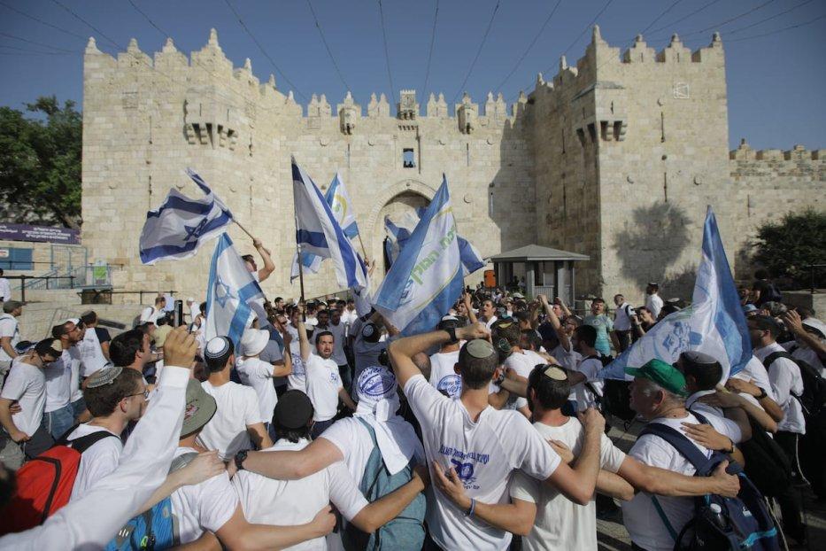 Israeli Jews wave the Israeli flag outside Damascus Gate in Jerusalem's Old City on 2 June 2019 [Faiz Abu Rmeleh/Anadolu Agency]