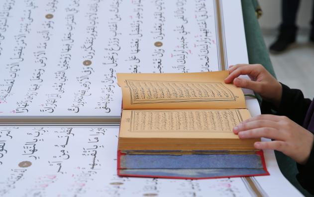 A Holy Quran, which has 70 kilograms weight and 71-98 centimetres size is on display at Istanbul's Camlica Mosque courtyard, during the 38th Book and Culture Fair, organized by Turkiye Diyanet Foundation (TDV), in Istanbul, Turkey on 1 June, 2019 [İsa Terli/Anadolu Agency]