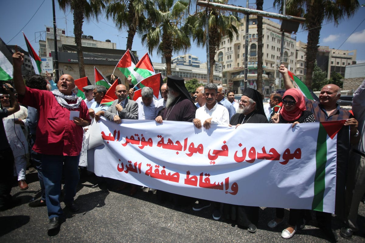 """Palestinians hold a banner as they gather to protest against a conference, which is the workshop, scheduled for June 25 and 26, in Bahrain's capital Manama, related with a """"Deal of the Century"""" plan in Ramallah, West Bank on June 15, 2019. [Issam Rimawi - Anadolu Agency]"""
