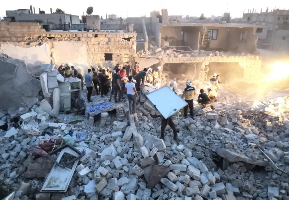 Civil defence members and locals conduct search and rescue works at a debris of a building after Assad Regime's warplanes carried out airstrikes over the de-escalation zone of Saraqib district in Idlib, Syria on June 22, 2019. [Hasan Muhtar - Anadolu Agency]