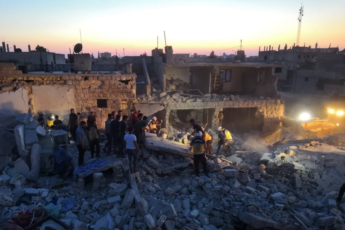Civil defence members and locals conduct search and rescue works at a debris of a building after Assad Regime's warplanes carried out airstrikes over the de-escalation zone of Saraqib district in Idlib, Syria on 22 June, 2019 [Hasan Muhtar/Anadolu Agency]