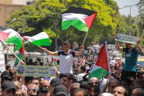 People hold flags during a demonstration against the US-led conference in Bahrain, on 26 June 2019 in Gaza City, Gaza. [Ali Jadallah/Anadolu Agency
