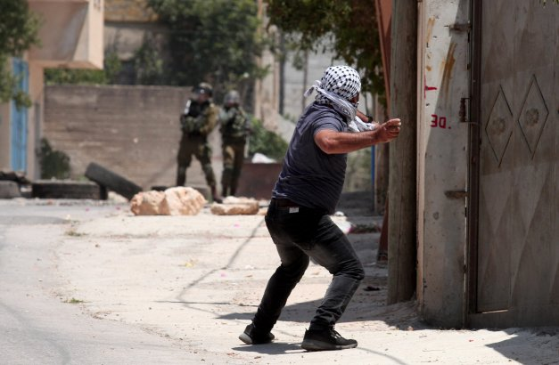 A demonstrator prepares to throw a stone in response to Israeli soldiers' intervention in Palestinians demonstrating against the Jewish settlements and the separation wall on 28 June 2019 at Qafr Qaddum village in Nablus, West Bank. [Nedal Eshtayah/Anadolu Agency]