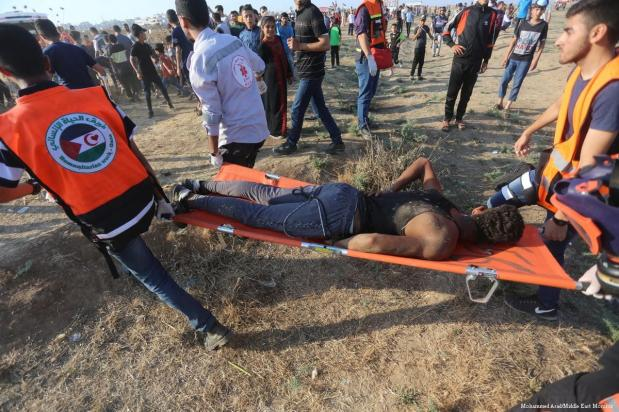 Palestinian medics carry away an injured protestor during the Great March of Return in Gaza on 14 June 2019 [Mohammad Asad/Middle East Monitor]
