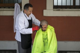 Imam Osman Gokrem (L) shaves and gives rough sleeper free haircuts at the historic Selime Hatun Mosque in Istanbul, Turkey on 29 June 2019 [Arif Hüdaverdi Yaman/Anadolu Agency]