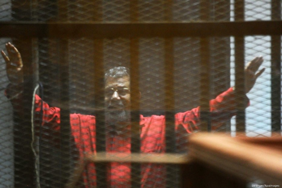Late former Egyptian president Mohammed Morsi sits behind bars during his trail on 21 March 2016 [Stranger/Apaimages]