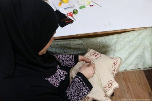 A Palestinian woman embroiders traditional Palestinian tapestry onto a piece of cloth, which will later be sold.