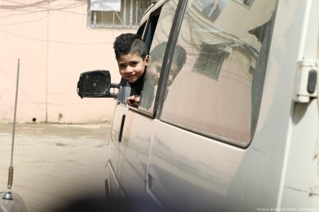 A young boy pokes his head out of a passing van.