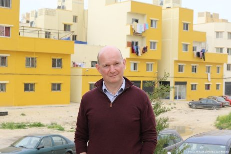 John Whyte, project manager for UNRWA's Nahr Al-Bared reconstruction, stands in front of some of the newly-reconstructed buildings.