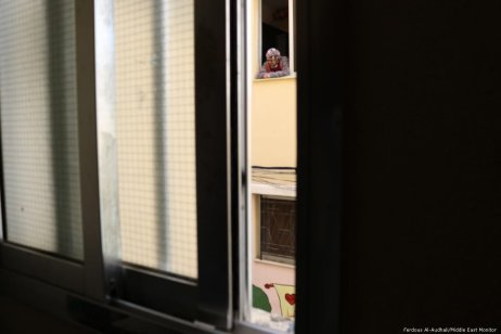 A resident of Nahr Al-Bared looks out of her newly-rebuilt home onto the street below.