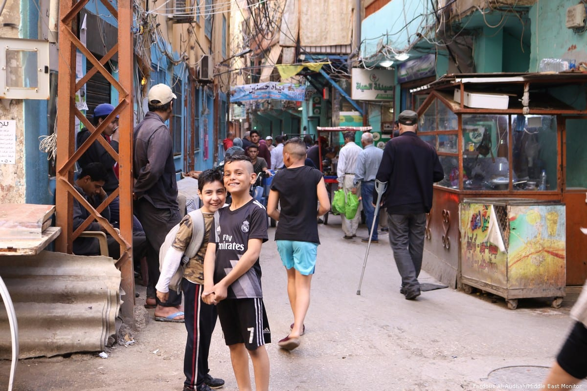 Two young boys smile and pose for the camera in Shatila camp