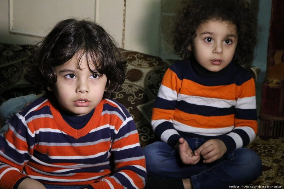 Two of Um Ahmed's grandchildren watch as their grandma speaks.