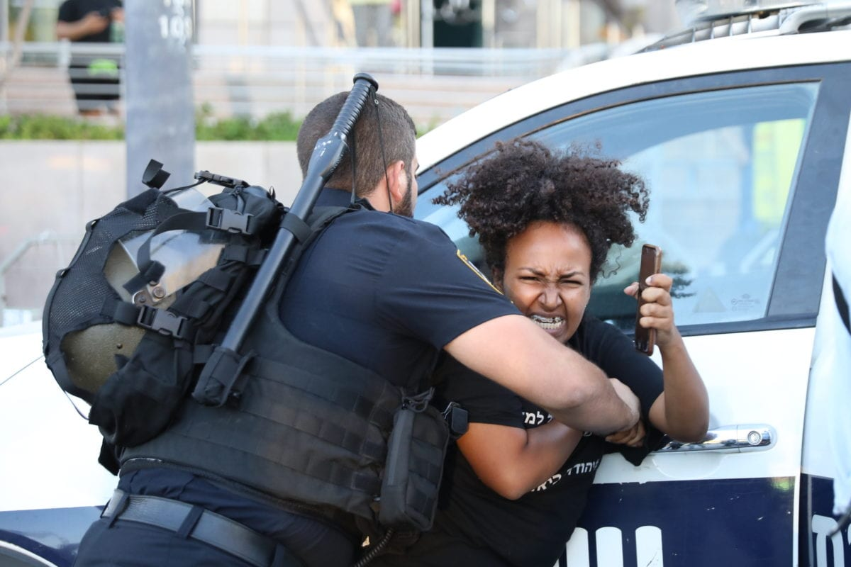 Security forces take a protester into custody during a protest against the killing of Solomon Tekah, a young man of Ethiopian origin, who was killed by an off-duty police officer, near Azrieli Tower in Tel Aviv, Israel on July 03, 2019. [Oren Ziv - Anadolu Agency]