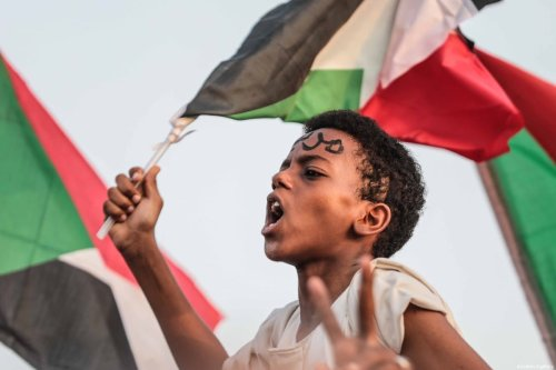 A young Sudanese boy is seen at a protest demanding a civilian transition government in front of military headquarters in Khartoum, Sudan on 5 July 2019 [Mahmoud Hjaj/Anadolu Agency]