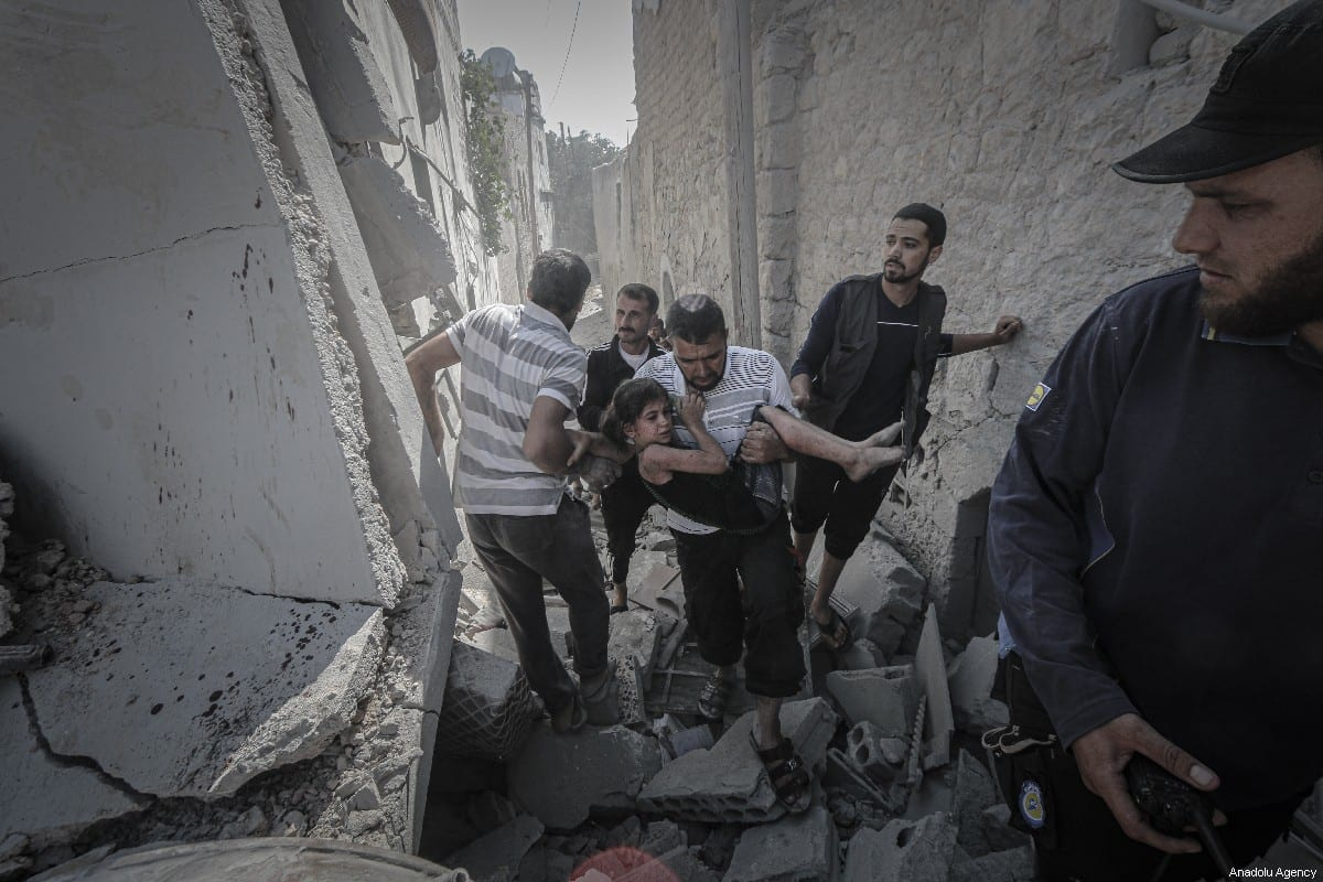A Syrian man carries an injured girl following air strikes carried out by the Syrian regime on 12 July 2019 [Muhammed Said/Anadolu Agency]