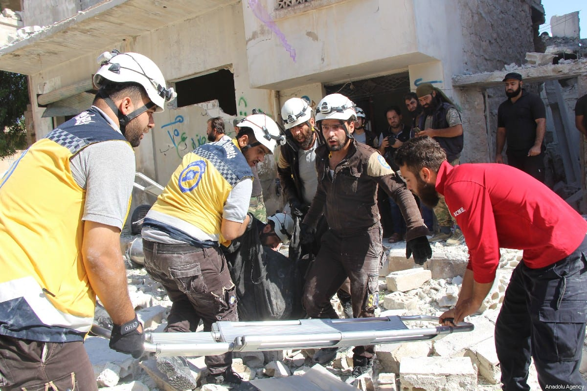 Civil defence crews remove a dead body from the scene after airstrikes by Assad Regime and Russia's warplanes hit the de-escalation zone of Kafriya village in Idlib, Syria on 13 July 2019 [Ahmet Weys/Anadolu Agency]