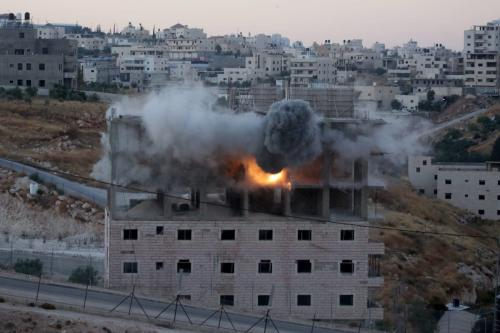 Smoke rises as Israeli forces begin to raze a building on the grounds that the building was close to the wire barriers, which is continuation of the separation wall, in the neighborhood of Wadi Homs in East Jerusalem on 22 July 2019. [Issam Rimawi - Anadolu Agency]