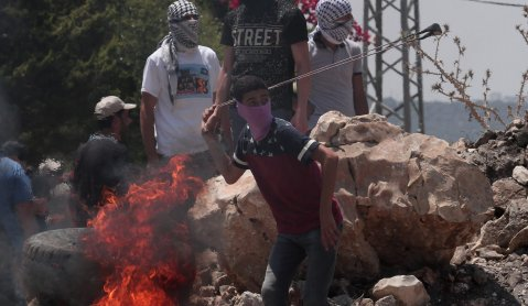 A Palestinian demonstrator throws a rock using slingshot in response to Israeli forces' intervention during a protest against the construction of Jewish settlements and the separation wall in Qafr Qaddum village in Nablus, West Bank on 26 July 2019 [Nedal Eshtayah/Anadolu Agency]