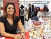 """Palestinian chef Joudie Kalla seen at the MEMO stall signing copies of her latest cookbook """"Baladi"""" at the Palestine Expo 2019 on 6 July 2019 in London, UK [Middle East Monitor]"""