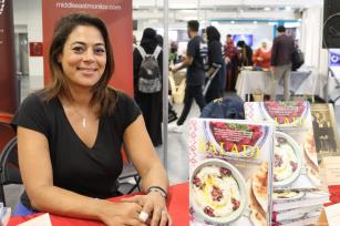 "Palestinian chef Joudie Kalla seen at the MEMO stall signing copies of her latest cookbook ""Baladi"" at the Palestine Expo 2019 on 6 July 2019 in London, UK [Middle East Monitor]"