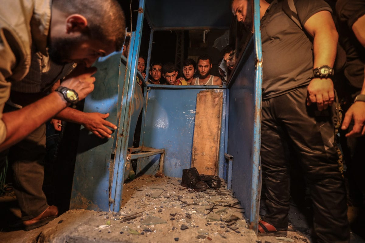 Residents inspect the scene after a blast at a check point on Al Rasheed Street in Gaza City on 27 August 2019. [Ali Jadallah - Anadolu Agency]