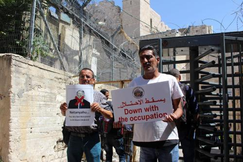 Palestinian protesters hold placards prior to the arrival of the Israeli prime minister to attend a state memorial ceremony at the Ibrahimi mosque, in the West Bank city of Hebron on 4 September 2019. [Mosab Shawer-Apaimages]