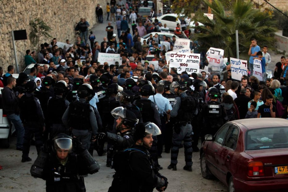 Palestinian protesters hold placards in front of Israeli border police, during a demonstration at the east Jerusalem Arab neighborhood of Issawiya, 12 November 2014. [Muammar Awad-Apaimages]