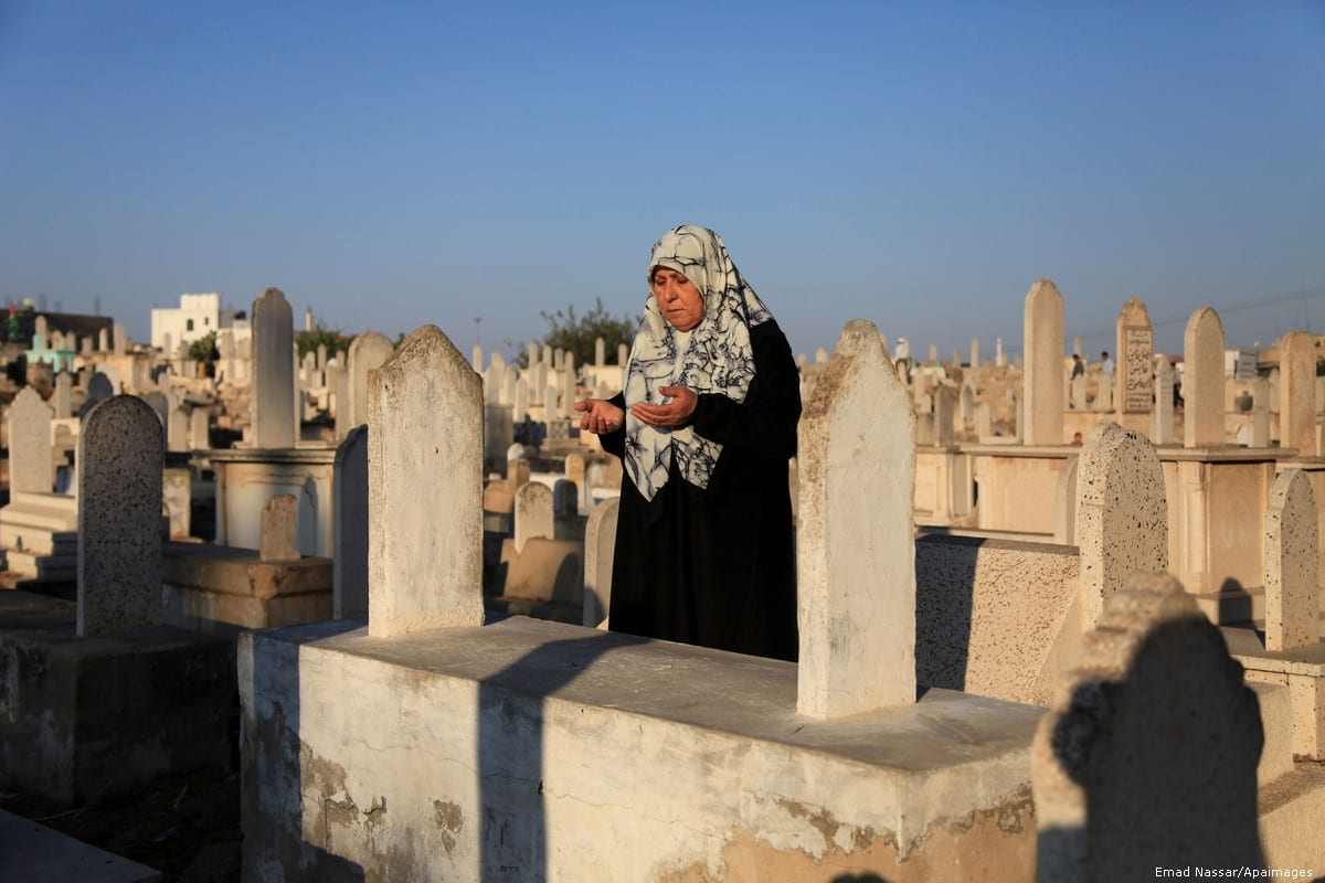 A Palestinian woman prays at the grave of a relative in a cemetery in Gaza on 15 October 2013 [Emad Nassar/Apaimages]