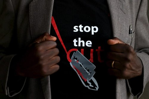 "A man shows the logo of a T-shirt that reads ""Stop the Cut"" referring to Female Genital Mutilation (FGM) during a social event advocating against harmful practices such as FGM at the Imbirikani Girls High School in Imbirikani, Kenya, 21 April 2016. [REUTERS/Siegfried Modola]"