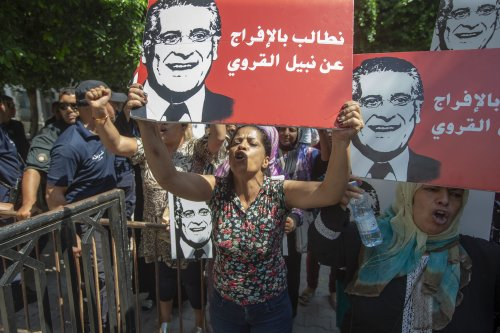 Supporters of presidential candidate Nabil Karoui carry placards with his image and slogans in his favour as they rally in front of the tribunal in the Tunisian capital Tunis asking for his release from prison on 3 September 2019. [Yassine Gaidi - Anadolu Agency]