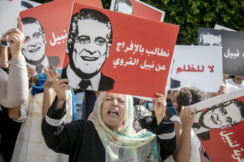 Supporters of presidential candidate Nabil Karoui carry placards with his image and slogans in his favour as they rally in front of the tribunal in the Tunisian capital Tunis asking for his release from prison on 3 September 2019. [Nacer Talel - Anadolu Agency]