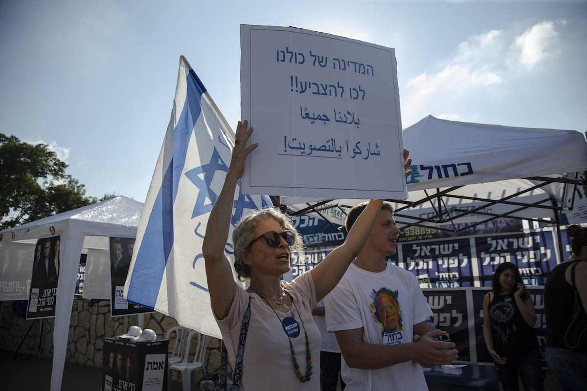 "A women holds a banner reading ""this country is ours, vote"" during the Israeli legislative elections, in Tel Aviv, Israel, on 17 September 2019. [Faiz Abu Rmeleh - Anadolu Agency]"