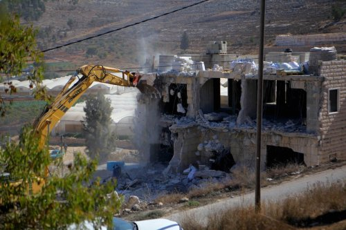 Israeli authorities use heavy machinery to demolish a two-storey building belonging to Palestinians, allegedly for being unauthorized, in Hebron, West Bank on September 25, 2019. ( Mamoun Wazwaz - Anadolu Agency )