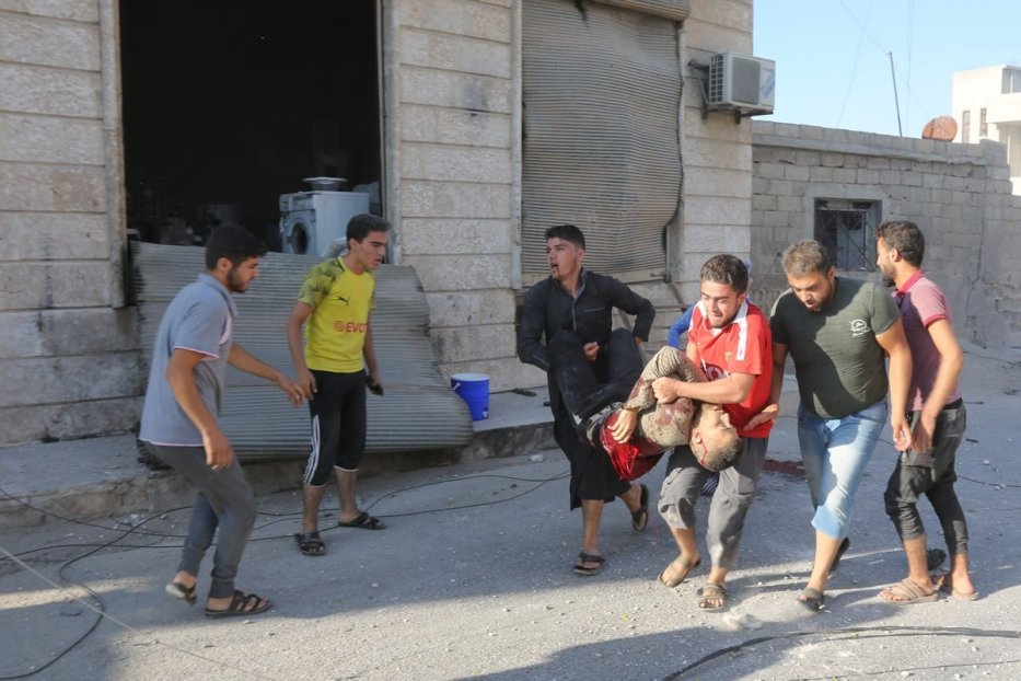 A wounded man is carried away from a site that was hit by air strikes carried out by the Assad Regime in Idlib, Syria on 27 August 2019 [Izeddin Idilbi/Anadolu Agency]