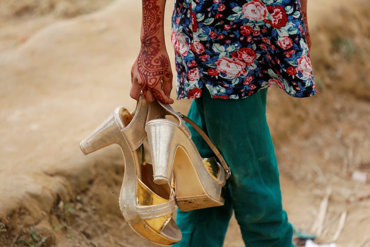 A Bangladeshi girl carries her sister's shoes near Cox's Bazar, Bangladesh on 8 December 2017. [REUTERS/Damir Sagolj]