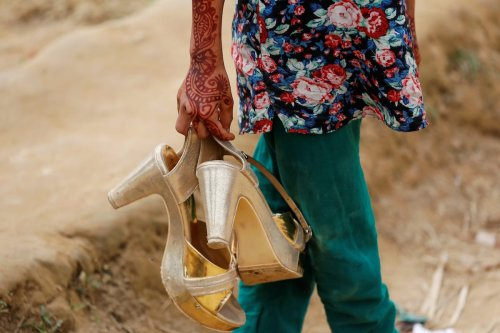 A Bangladeshi girl carries her sister's shoes near Cox's Bazar, Bangladesh on 8 December 2017. [REUTERS/Damir Sagolj]