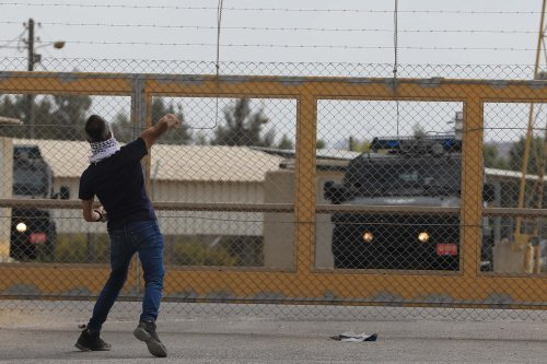A Palestinian throws a stone to Israeli forces as Israeli security forces intervene them during a demonstration to show solidarity with Palestinian prisoners held in Israeli jails, near the Ofer Prison in Ramallah, West Bank on 5 October, 2019 [Issam Rimawi/Anadolu Agency]