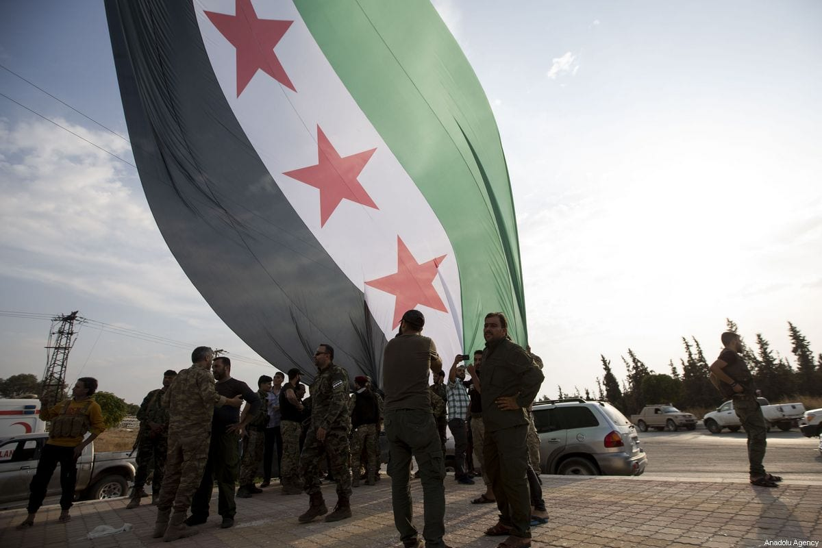 Syrian National Army (SNA) members hang a Syrian National Army flag on 17 October 2019 in Tal Abyad, Syria. [Anadolu Agency - Anadolu Agency]