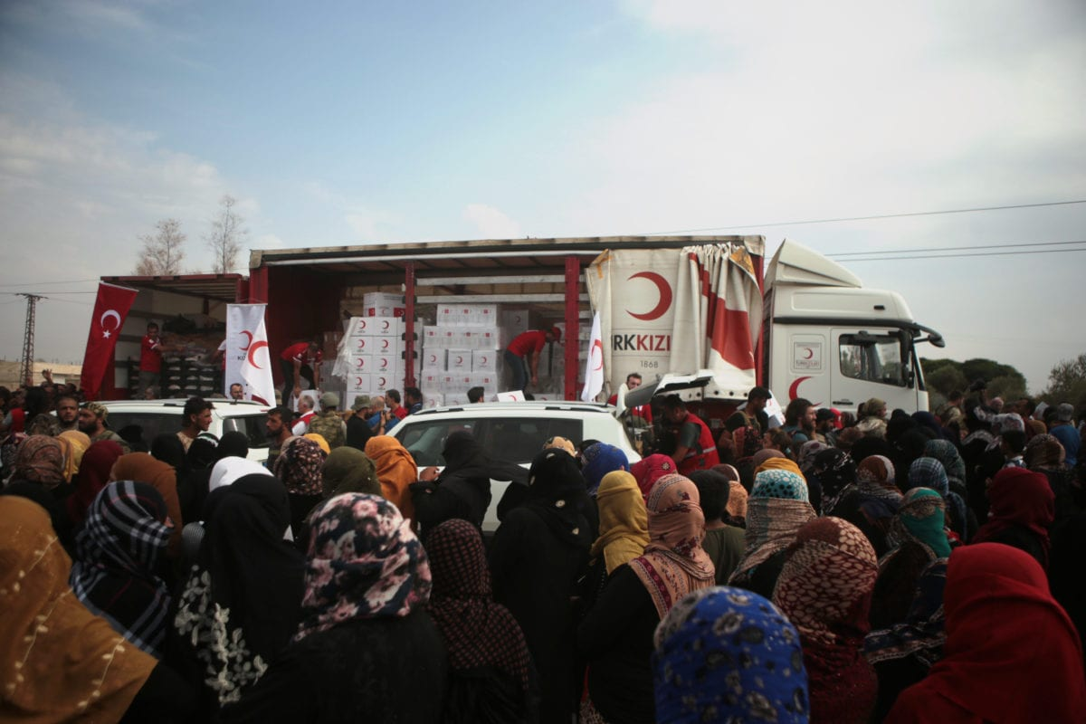 Members of Turkish Red Crescent distribute humanitarian aids to the civilians in Tal Abyad, Syria after the city center was cleared from PKK, within Turkey's Operation Peace Spring as the flow of life returns to normal in northern Syria, in Tal Abyad, Syria on 19 October 2019. [Ömer Alven - Anadolu Agency]