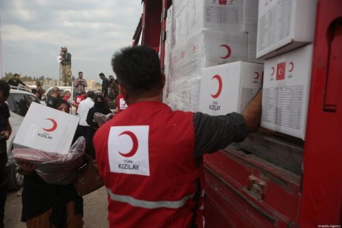 Members of Turkish Red Crescent distribute humanitarian aids to the civilians in Tal Abyad, Syria on October 19, 2019 [Ömer Alven/Anadolu Agency]