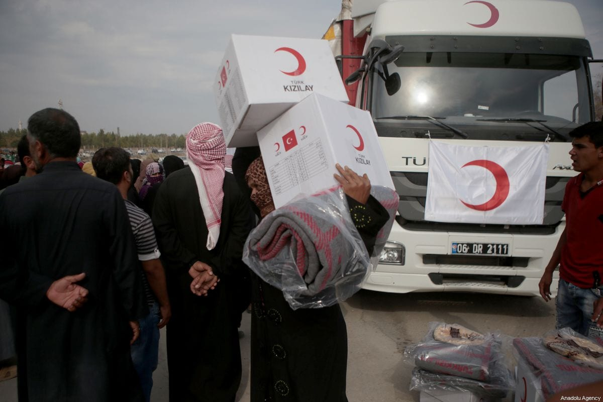 Civilians carry humanitarian aids distributed by Turkish Red Crescent in Tal Abyad, Syria on October 19, 2019. [Ömer Alven - Anadolu Agency]