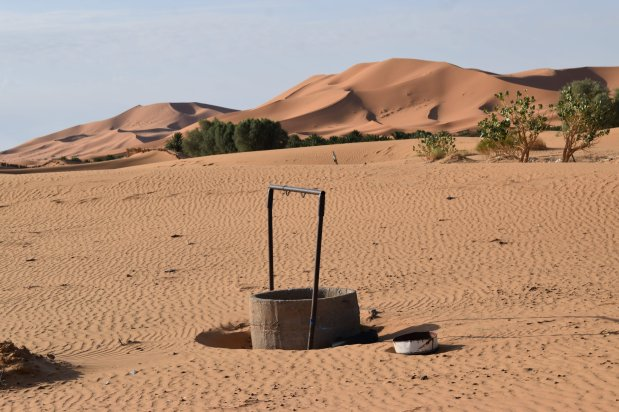 An old well stands alone in the sand of Morocco's desert region, with the high rolling dunes of the Sahara seen in the background