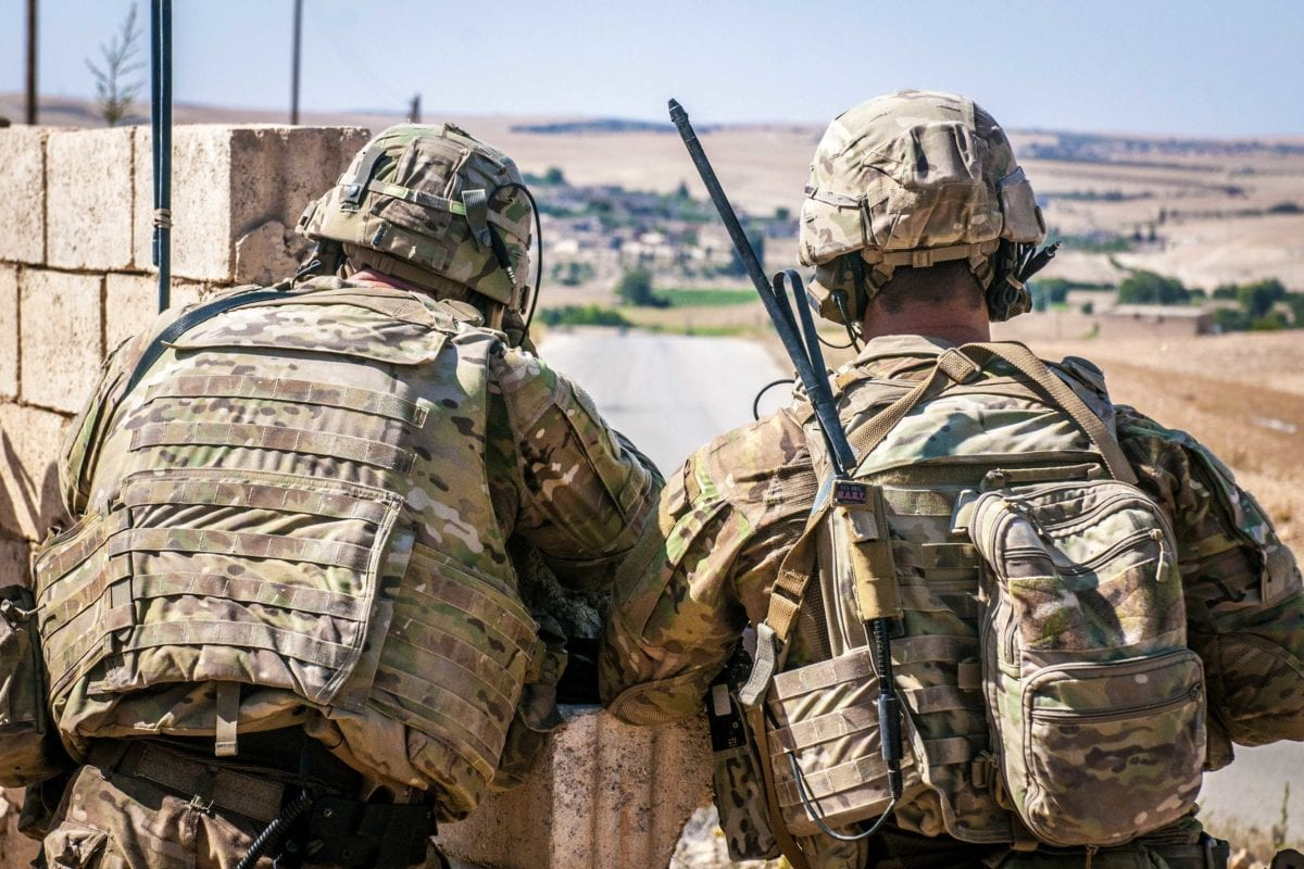 Two US Soldiers keep an eye on the demarcation line during a security patrol outside Manbij, Syria, on 26 June 2018. [US Army - Staff Sgt. Timothy R. Koster]