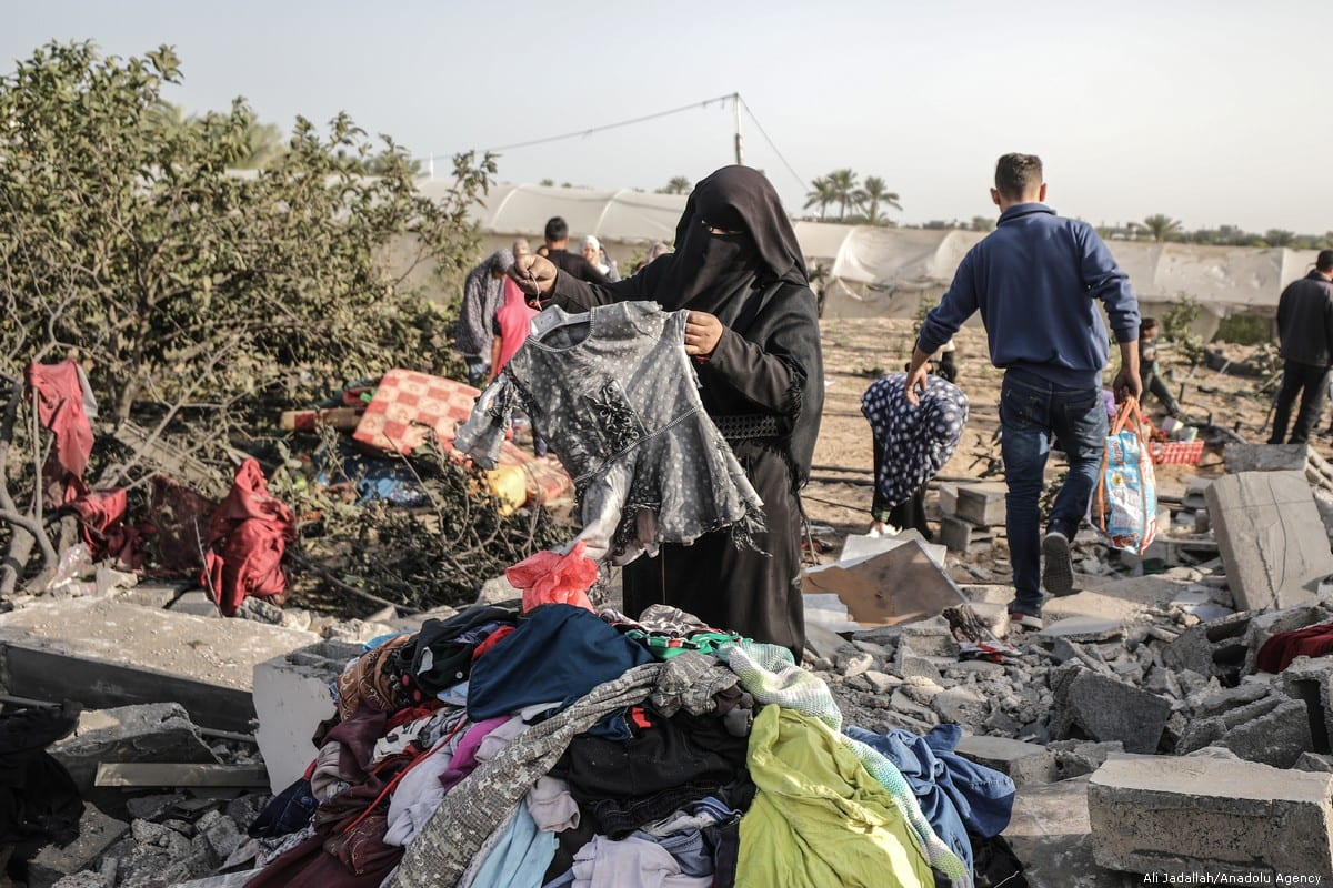 Palestinians sort though the damage done to their belongings following air strikes carried out by Israel in Gaza on 13 November 2019 [Ali Jadallah/Anadolu Agency]