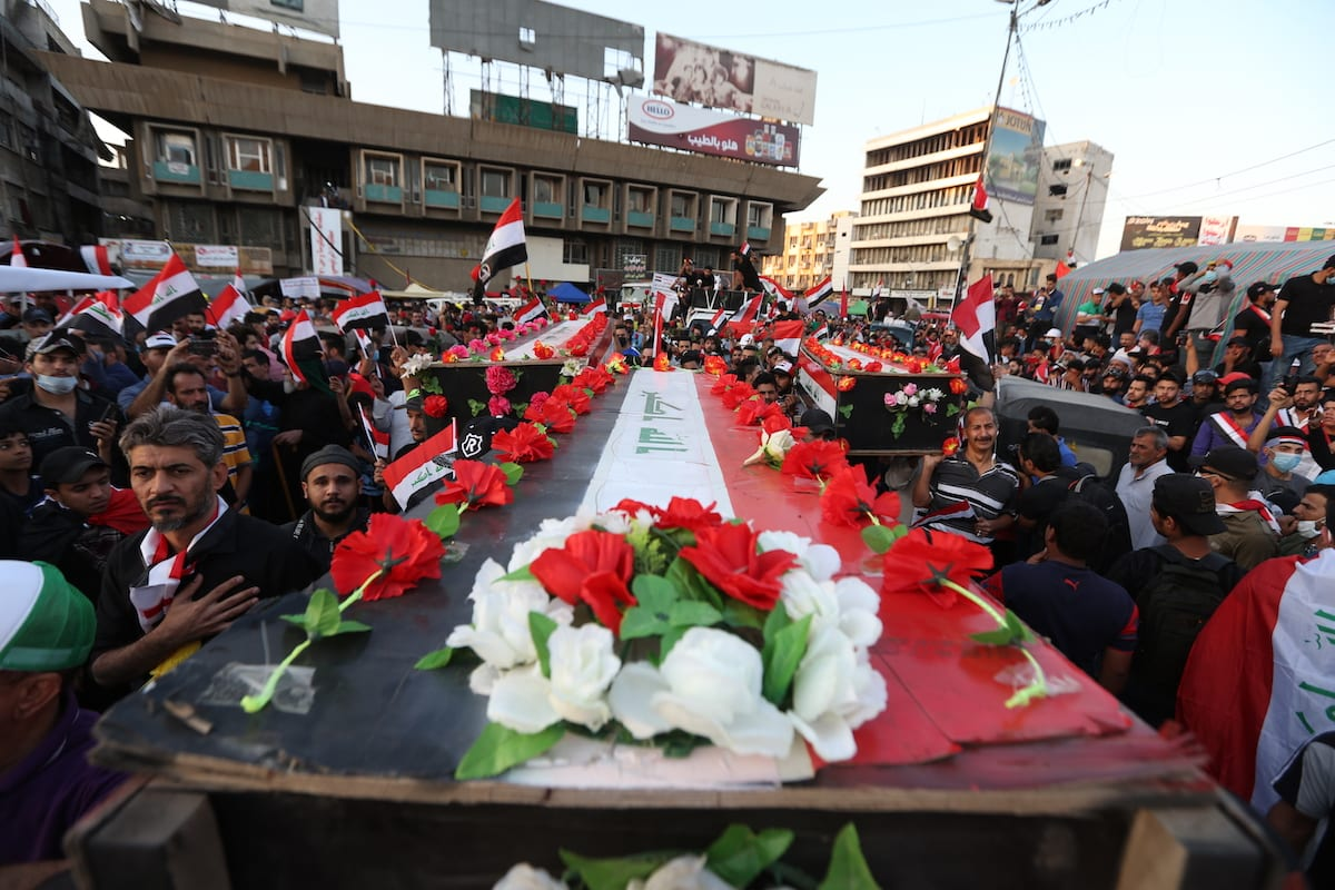 Iraqi protestors carry a mock up coffin for victims, who lost their lives in protests, as they gather at Tahrir Sqaure during ongoing anti-government demonstrations economic reforms and overhaul of the political system in Baghdad, Iraq on 5 November 2019. [Murtadha Sudani - Anadolu Agency]