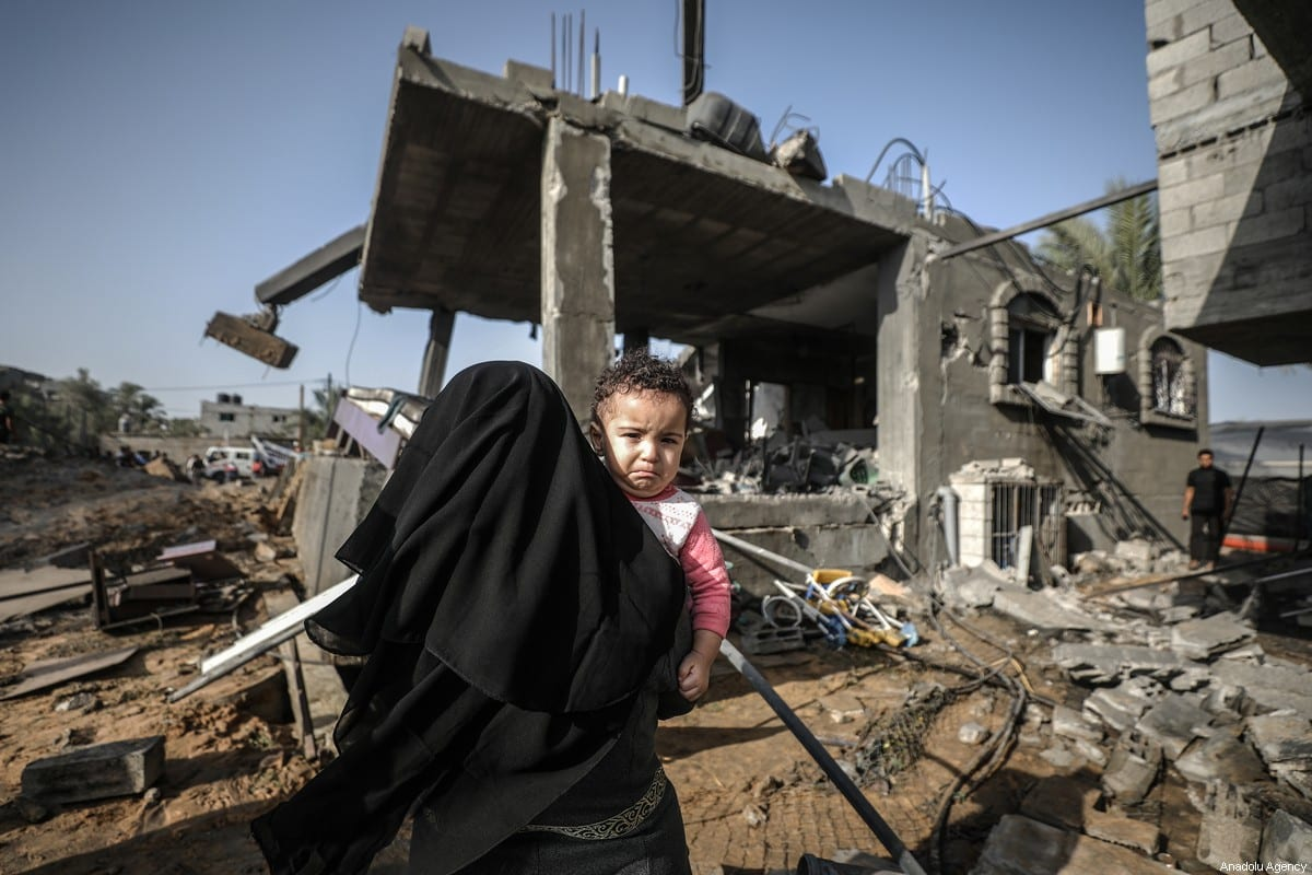 A woman holds a baby near a destroyed house after Israeli airstrikes hit Abu Hadayids' home in Rafah, Gaza on November 13, 2019 [Ali Jadallah / Anadolu Agency]
