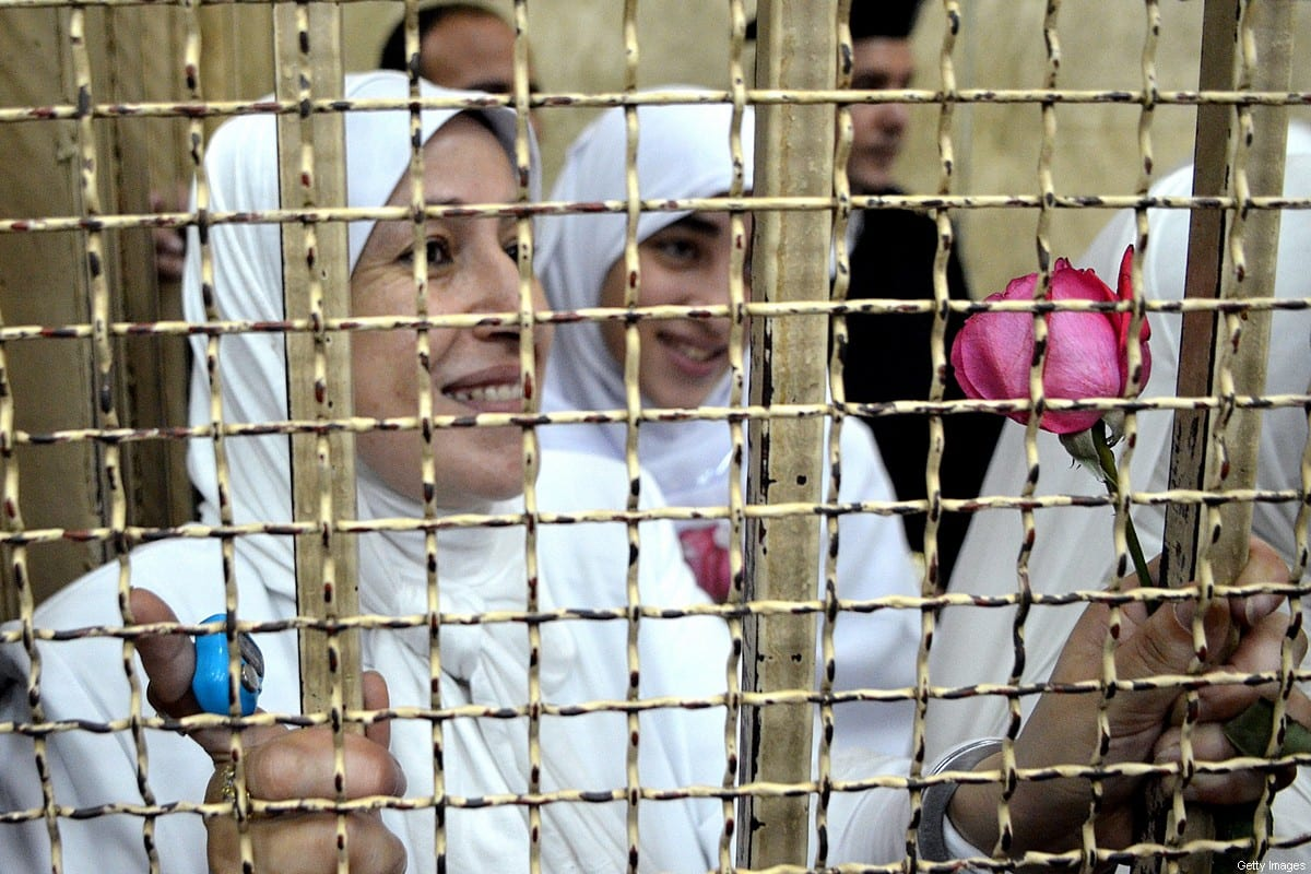 Egyptian women members of the Muslim Brotherhood hold roses as they stand in the defendants' cage dressed in prison issue white during their trial in at the court in the Egyptian Mediterranean city of Alexandria on 7 December 2013. [AFP via Getty Images]