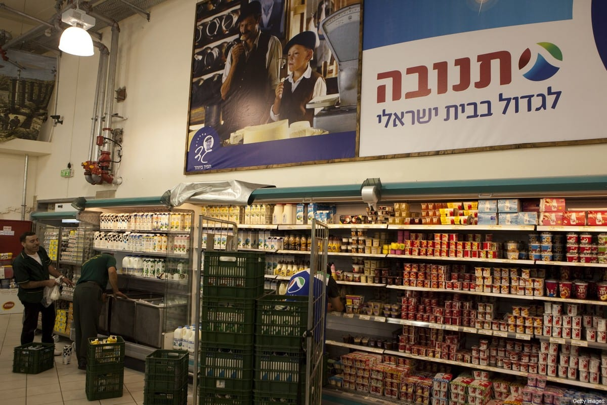 """TO GO WITH STORY BY PATRICK MOSER- Two Palestinians unload goods in a large Jewish owned supermarket located at the Gush Etzion junction in the Palestinian West Bank on July 4, 2010. Israeli settler and industrialist Avi Elkayam, 35, has no patience with the Palestinian boycott of settlement products. """"It's economic terrorism,"""" he shouts shaking his fist. AFP PHOTO/MENAHEM KAHANA (Photo credit should read MENAHEM KAHANA/AFP via Getty Images)"""