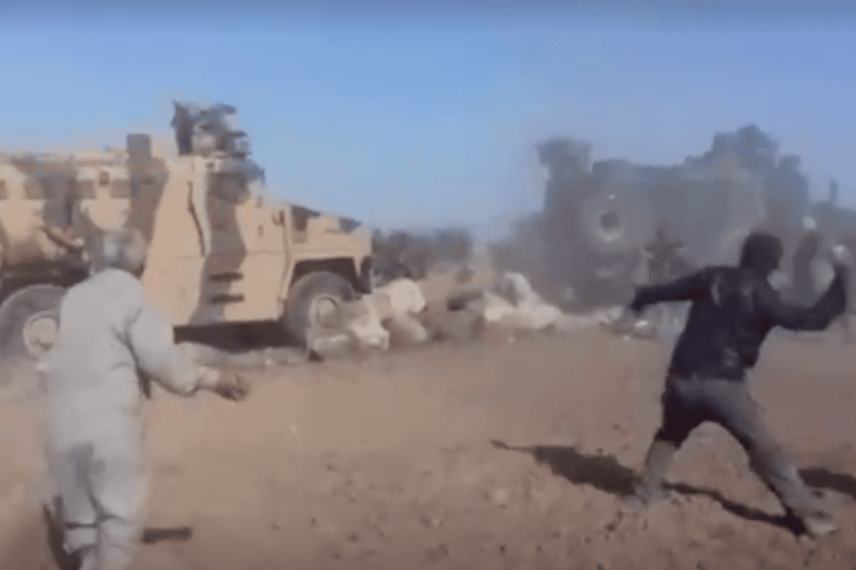 Protesters hurling rocks at a military convoy near the town of Kobani, Syria [Twitter]